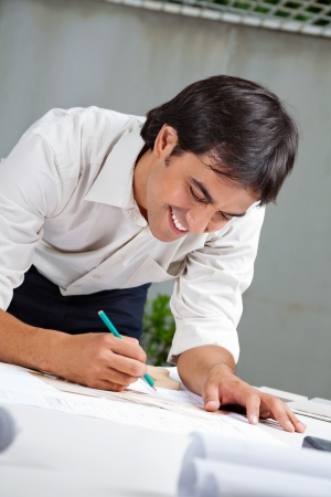 Young male architect smiling while working on blueprint photo
