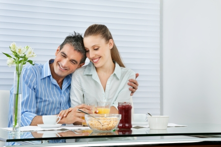 Happy couple having breakfast together at the table photo