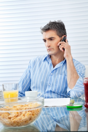 having breakfast: Mid adult man attending phone call while having breakfast at the table