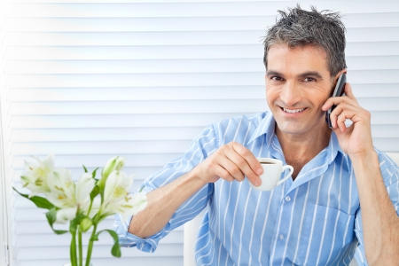 Portrait of handsome middle aged man having cup of tea while receiving phone call photo