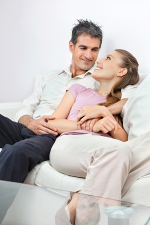 Happy couple looking at each other while sitting comfortably on sofa at home photo