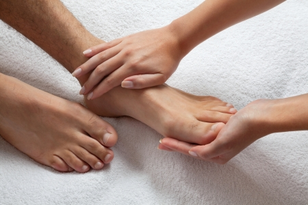 healing: Close up of female masseuse giving a foot massage to man