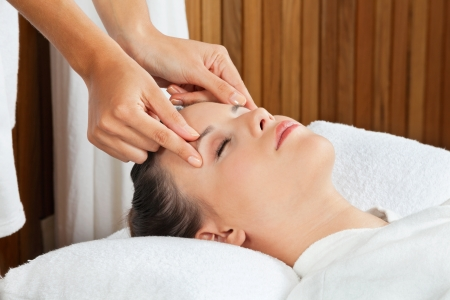 head massage: Pretty young female receiving a head massage at health spa
