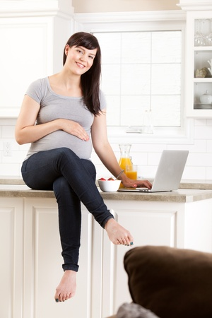 Healthy pregnant woman sitting on kitchen counter eating snack photo