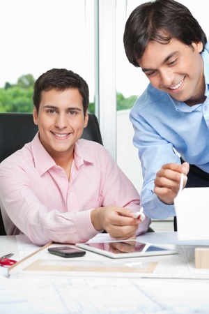 Portrait of happy young male architect at desk with colleague standing beside Stock Photo - 14943516