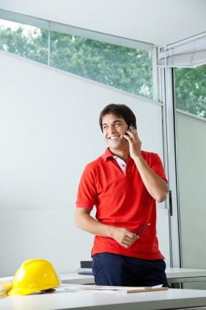 answering phone: Arquitecto masculino joven que sonr�e al responder llamada telef�nica