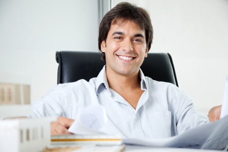 tangible: Portrait of happy young male architect with blueprint sitting in office chair