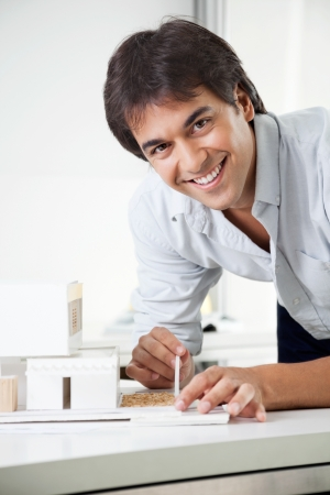 tangible: Portrait of young male architect smiling while creating a model house