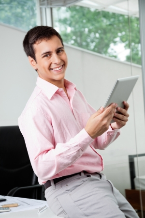 Portrait of happy young male business executive holding digital tablet photo
