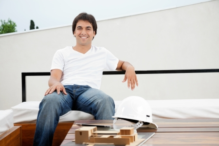 scale model: Portrait of a relaxed young male architect with hardhat and model structure on table