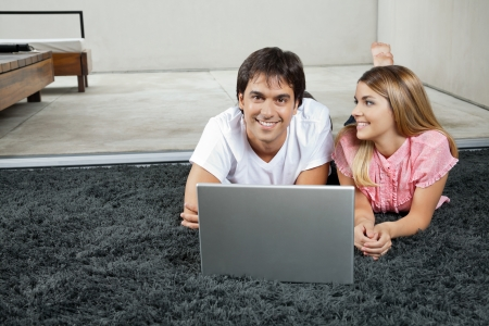 Portrait of happy young man lying on rug with laptop while woman looking at him photo
