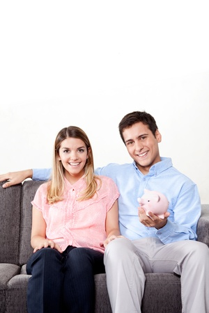 Young couple with a piggy bank sitting on couch photo