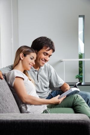 Young couple reading a book together while sitting on sofa at home photo