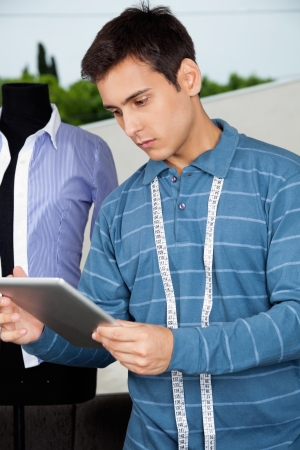 Young male tailor in casual t-shirt with measuring tape around neck holding tablet PC photo