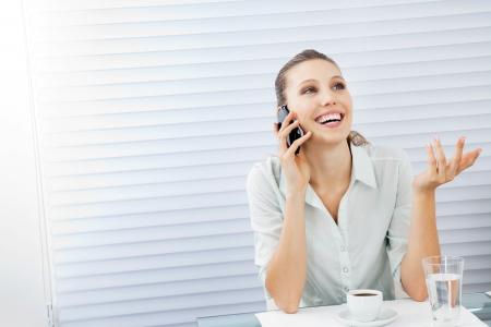 answering phone: Joven empresaria feliz respondiendo a la llamada de tel�fono mientras se est� sentado en la mesa