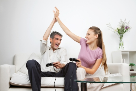video game: Couple giving a high-five to each other while having great time playing video game together