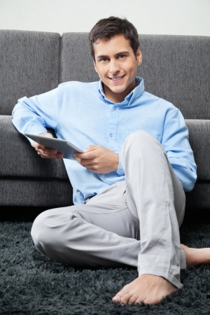 barefoot man: Portrait of young man in formal wear sitting comfortably on rug with digital tablet