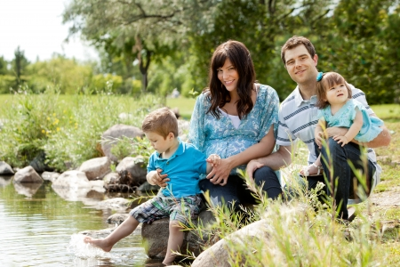 Happy similing young family sitting by lake photo