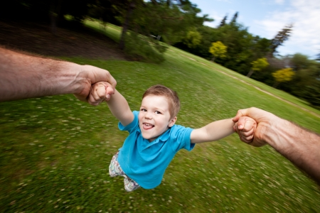 Motion blur of father holding onto son s arm while spinning  Sharp focus on eyes photo