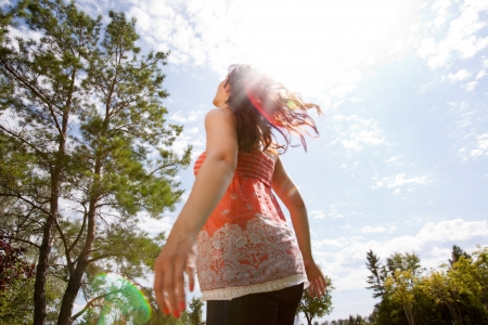 Happy pregnant woman looking to sky with arms back in park Stock Photo - 15075685
