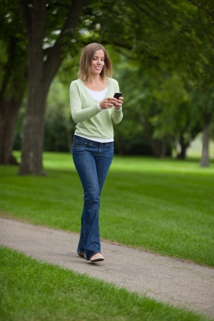 updates: Full length of a young woman text messaging as she walks in park