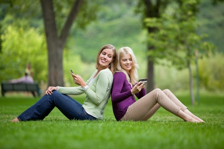 cellular telephone: Side view of happy young female friends with cellphones sitting back to back in park