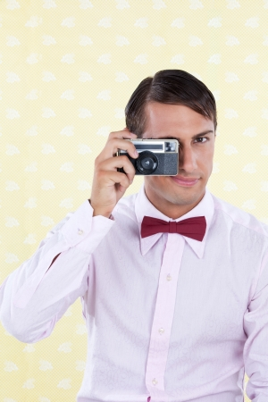 viewer: Male using old retro camera, looking at viewer