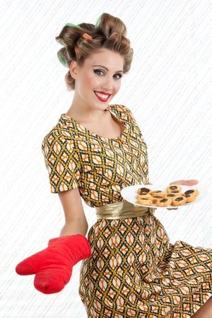 Retro femme avec des biscuits regardant la caméra avec le sourire Banque d'images