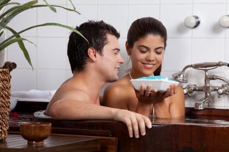 bath tub: Couple in bath tub holding bath salt in bowl  Stock Photo