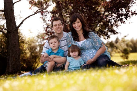 young family: Portrait of young family in park with pregnant mother