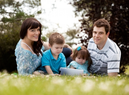 Happy young family outdoors with digital tablet photo