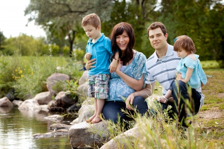family park: Portrait of happy good looking family near a lake in a park Stock Photo