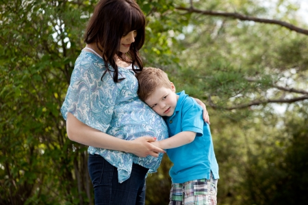 Young son listening to belly of pregnant outdoors in park photo