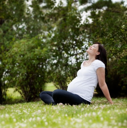 Happy attractive pregnant woman in park leaning back enjoying the sun Stock Photo - 15101129