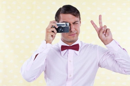 Man looking through old camera making peace sign Stock Photo - 15347745