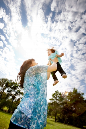 Pregnant mother in third trimester throwing daughter up in the air photo