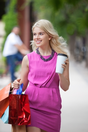 Happy young shopaholic woman with bags and disposable coffee cup walking on sidewalk photo