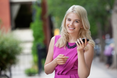 Portrait of a beautiful young woman holding mobile phone photo