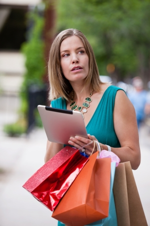 lost city: Woman shopping in city with digital tablet