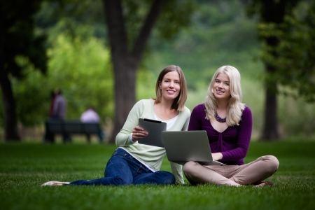 Smiling young women looknig at camera with computer and digital tablet in hand photo