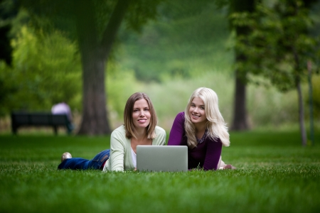 Young women using laptop in park, looking at camera photo