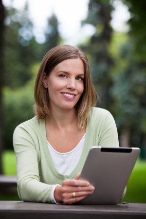 Woman holding Digital Tablet in park  photo