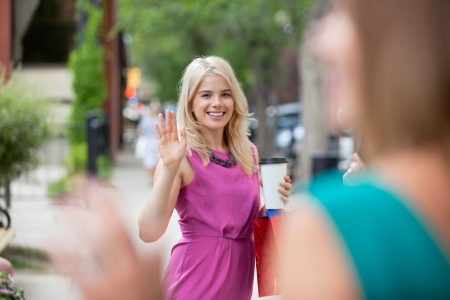 Happy young woman with disposable coffee cup waving to female friend photo