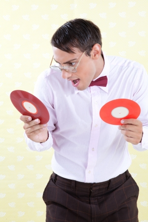 bowtie: Man looking at vinyl record with excited expression Stock Photo