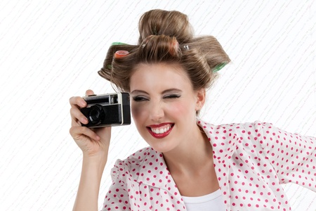Portrait of retro styled attractive woman taking photo with 35mm camera photo