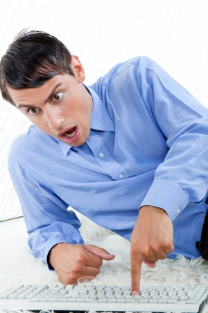 Surprised man with keyboard leaning on rug  photo