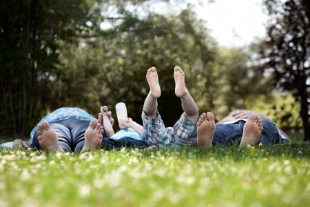 Young family with two kids and pregnant mother laying down in park with feet towards camera photo