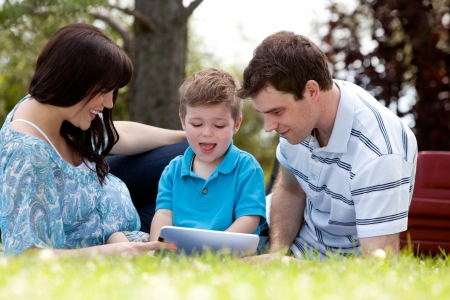 Happy beautiful young family in park with digital tablet Stock Photo - 15347750
