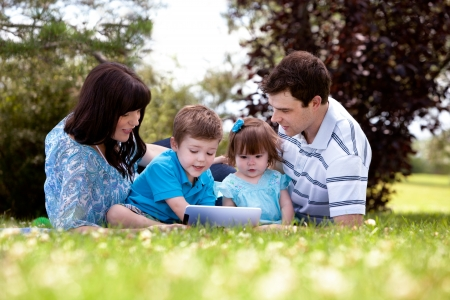 Happy family of four using a digital tablet outdoors photo