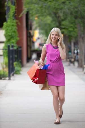 sidewalk talk: Full length of a happy young woman with shopping bags using cell phone while walking on sidewalk